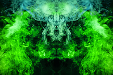 Photo pour Fantasy print for clothes: t-shirts, sweatshirts.  Colorful green and yellow  smoke in the form of a skull, monster, dragon on a black isolated background. Background from the smoke of vape - image libre de droit