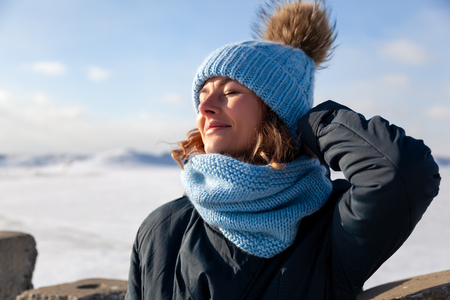 Foto de Portrait beauty woman model on winter background. Beautiful modern  young woman wearing blue knitting hat  warm hands, smile, look at camera on a walk on the frozen sea in winter - Imagen libre de derechos