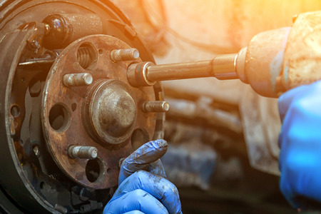 Photo pour Close-up replacement of the old front brake disc, brake caliper and hub nut on a car raised on a lift with a pneumatic wrench in a car repair shop. Auto mechanic repair. - image libre de droit