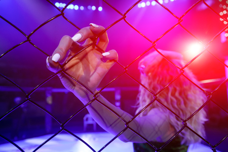 Photo pour Rear view of a ring girl holds her hand on a metal grid in an octagonal scene. Pretty woman in the sports of mixed martial arts at the MMA tournament competitions. The concept of fight without rules - image libre de droit