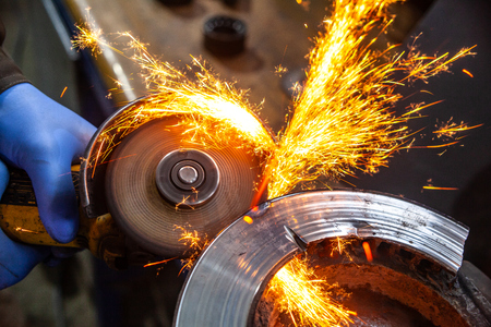 Photo for A close-up of a car mechanic using a metal grinder to cut   bearing in an auto repair shop, bright flashes flying in different directions. Work of auto mechanics. - Royalty Free Image