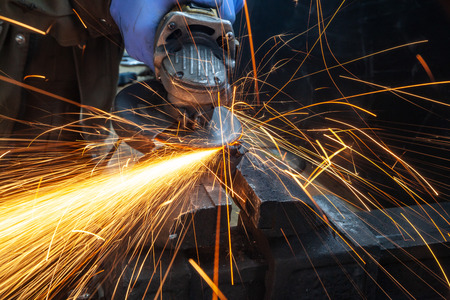 Photo for Close-up on the sides fly bright sparks from the angle grinder machine. A young male welder in a white working gloves grinds a metal product with angle grinder in the garage - Royalty Free Image
