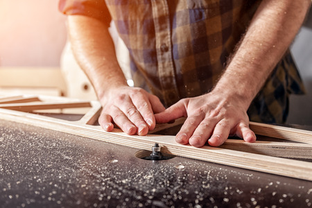 Photo for A young man carpenter builder in work clothes processing a wooden board with a milling machine in the workshop, around a lot of equipment, wooden boards. Home repair concepts. - Royalty Free Image
