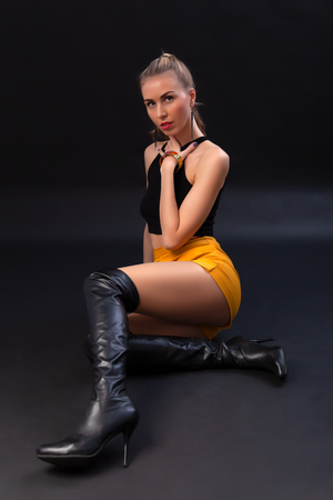 Photo for Young and sexy amazing blonde woman with glamorous makeup, wearing in a black leather jacket, black top, short skirt and boots posing in studio with dark background - Royalty Free Image