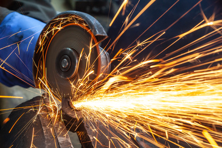 Foto de Close-up on the sides fly bright sparks from the angle grinder machine. A young male welder in a white working gloves grinds a metal product with angle grinder in the garage - Imagen libre de derechos