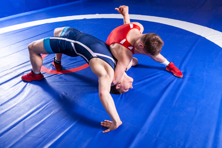 Photo pour Two young sportsmens wrestlers in red and blue uniform wrestling against wrestling carpet, view above. - image libre de droit