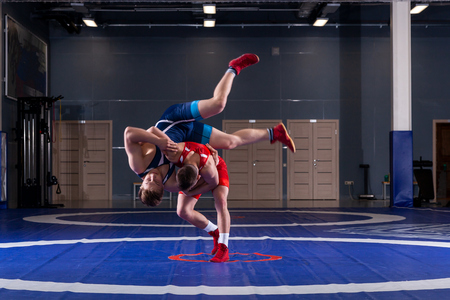 Photo pour Two young men in blue and red wrestling tights are wrestlng and making a hip throw on a yellow wrestling carpet in the gym. The concept of fair wrestling - image libre de droit
