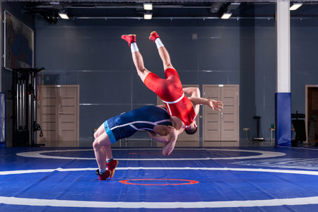 Photo pour Two young men in blue and red wrestling tights are wrestlng and making a suplex wrestling on a yellow wrestling carpet in the gym. The concept of fair wrestling - image libre de droit
