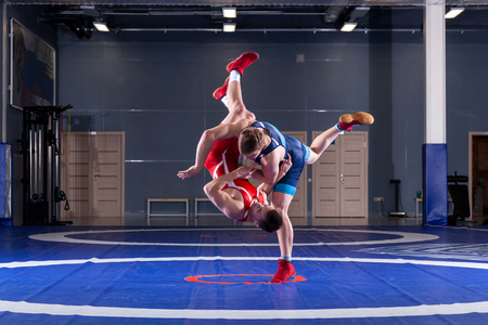 Photo pour Two strong wrestlers in blue and red wrestling tights are wrestlng and making a  making a hip throw  on a yellow wrestling carpet in the gym. Young man doing grapple. - image libre de droit