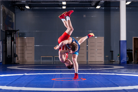 Photo pour The concept of fair wrestling. Two greco-roman  wrestlers in red and blue uniform wrestling   on a wrestling carpet in the gym.The concept of fair wrestling - image libre de droit