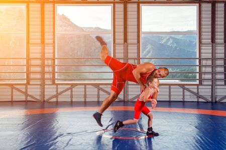 Photo pour The little boy in sport tights wrestler throws over the hip adult male wrestler on a wrestling carpet in the gym. The concept of child power and martial arts training. Teaching children Greco-Roman wrestling - image libre de droit