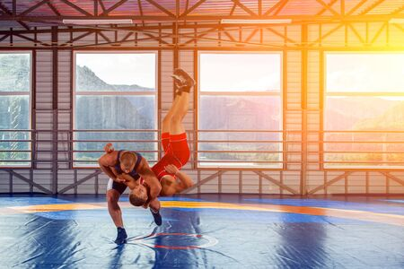 Photo pour Greco-Roman wrestling training, grappling. Two greco-roman  wrestlers in red and blue uniform making a suplex wrestling  on a wrestling carpet in the gym.The concept of male wrestling and resistance - image libre de droit