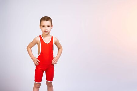 Photo pour Portrait of a little cheerful boy in a red wrestling tights holds his hands on his sides, looks confidently at the camera and poses on a white isolated background. The concept of a little fighter athlete - image libre de droit