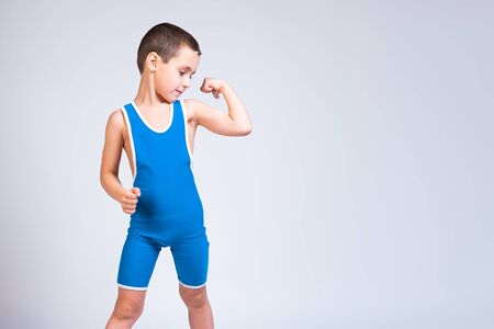 Photo pour Portrait of a little cheerful boy in a blue  wrestling tights shows biceps, looks confidently at him and poses on a white isolated background. The concept of a little fighter athlete - image libre de droit