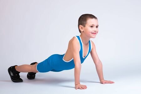 Photo pour Portrait of a little cheerful boy in a blue wrestling tights and p stands on his hands in a push-up pose, looks forward and poses on a white isolated background. The concept of a little fighter athlete - image libre de droit