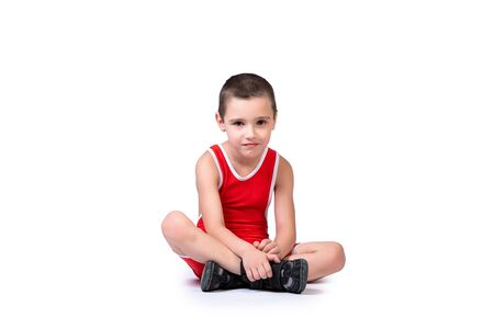 Photo for Sporty cheerful boy in a blue wrestling tights is ready to engage in sports exercises, is sitting on the floor on a white isolated background - Royalty Free Image