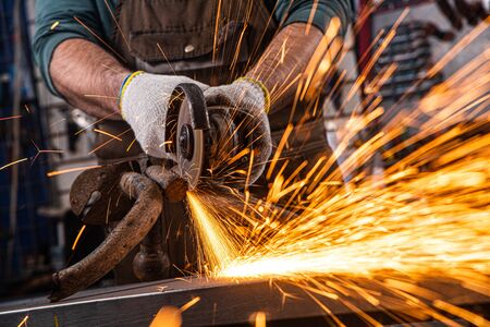 Photo pour Close-up on the sides fly bright sparks from the angle grinder machine. A young male welder in a white working gloves grinds a metal product with angle grinder in the garage - image libre de droit