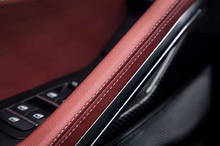 Photo pour Ð¡lose up of a door control panel with chrome handle on the car door, common black and red genuine leather in a new car. Arm rest in luxury car - image libre de droit