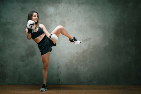 Photo for Young athletic woman boxer in shorts, short top and boxing gloves doing a kick above his head on dark gray background. Full length. Wall in background. - Royalty Free Image
