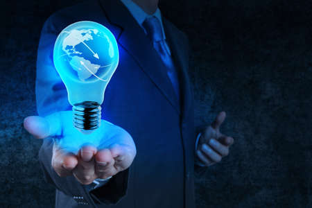 Photo for Businessman hand shows Light bulb with planet Earth social network as concept - Royalty Free Image