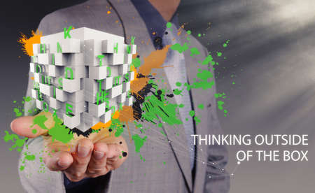 businessman hand shows word thinking outside the box and splash colors as concept