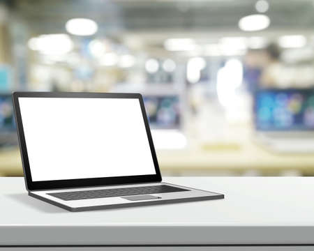 Laptop with blank screen on laminate table and blurred background