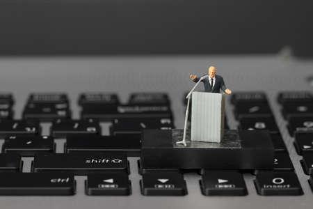 Foto de online conference concept-miniature speaker at Business Conference on laptop computer - Imagen libre de derechos