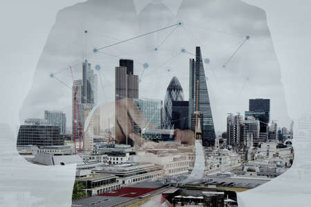 Double exposure of success businessman using smart phone and social media diagram with london city blurred