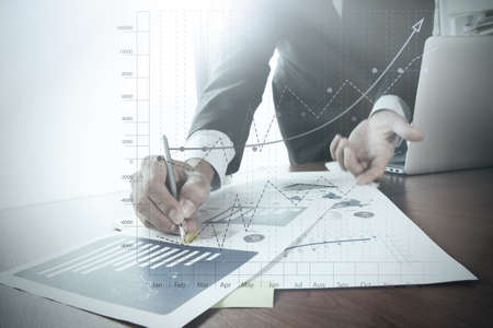 Photo pour close up of business man hand working on laptop computer with business graph information diagram on wooden desk as concept - image libre de droit