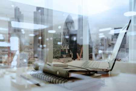 Foto de Office workplace with laptop and smart phone on wood table and london city blurred background - Imagen libre de derechos