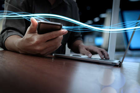 Foto de Waves of blue light and businessman using on smartphone and laptop computer as concept - Imagen libre de derechos