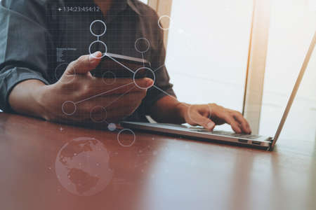Photo for businessman hand working and smart phone and laptop with social media diagram on wooden desk in office - Royalty Free Image