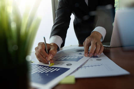 Foto de businessman hand working with new modern computer and business strategy documents with green plant foreground on wooden desk in office - Imagen libre de derechos