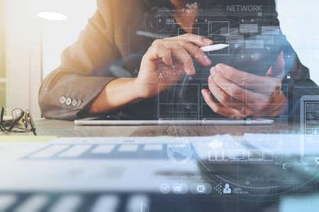 Foto per business documents on office table with digital tablet computer with smart phone and graph business digital diagram and businessman working in the background - Immagine Royalty Free