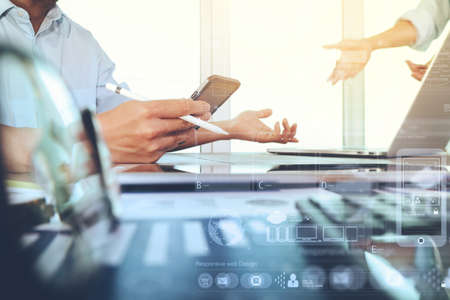 Photo pour business documents on office table with smart phone and laptop computer and graph business with social network diagram and two colleagues discussing data in the background - image libre de droit