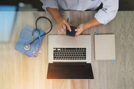 Photo pour top view of Medicine doctor hand working with modern computer and smart phone on wooden desk as medical concept - image libre de droit