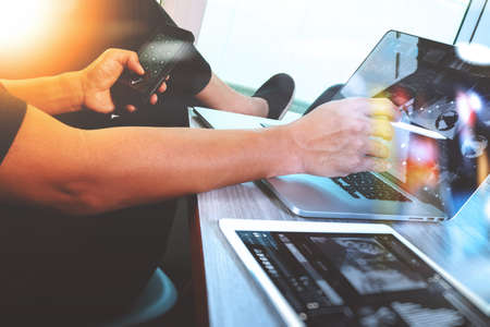 Foto de Website designer working digital tablet and computer laptop with smart phone and digital design diagram on wooden desk as concept - Imagen libre de derechos