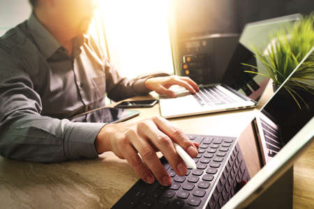 Foto de Outsource Developer working on marble Desk Working Laptop Computer Mobile Application Software and digital tablet dock smart keyboard,compact server,sun flare effect - Imagen libre de derechos