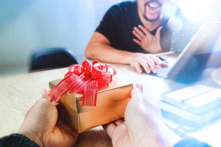 Foto de Gift Giving.business creative designer hand giving his colleague Christmas present in office,filter film effect - Imagen libre de derechos