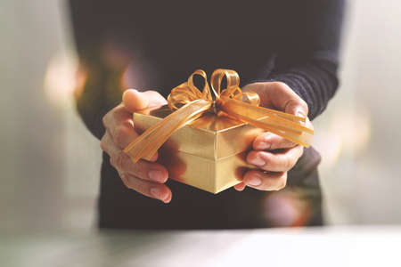 Photo pour gift giving,man hand holding a gold gift box in a gesture of giving.blurred background,bokeh effect - image libre de droit