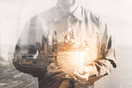 Double exposure of success businessman holding vase plant,tree, with London building,city,front view,filter effect