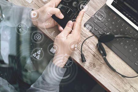 Photo pour top view of man hand using VOIP headset with digital tablet computer docking keyboard,smart phone,concept communication, it support, call center and customer service help desk on wooden table,virtual interface icons screen - image libre de droit