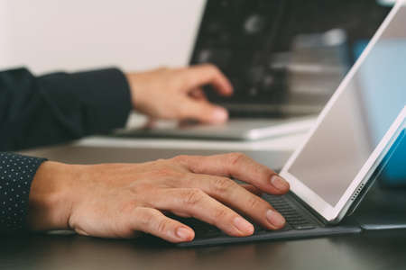 close up of businessman hand working with laptop and digital docking keyboard tablet computer in modern office with glass reflected view