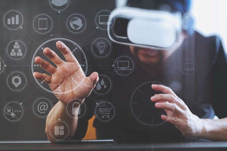 Photo pour businessman wearing virtual reality goggles in modern office with mobile phone using with VR headset with screen icon diagram - image libre de droit