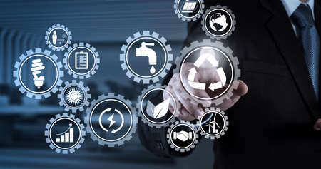 Foto de Sustainable development with icons of renewable energy and natural resources preservation with environment protection inside connected gears.Businessman hand pressing an imaginary button on virtual screen - Imagen libre de derechos
