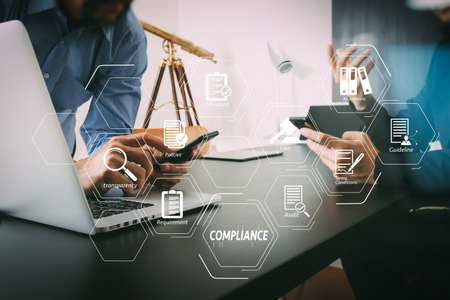 Foto de Compliance Virtual Diagram for regulations, law, standards, requirements and audit.co working team meeting concept,businessman using smart phone and digital tablet and laptop computer in modern office                                - Imagen libre de derechos