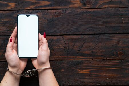 Photo pour Top view woman hands in handcuffs hold a smartphone with an blank screen for text. The concept of internet addiction, social networking and gadgets. - image libre de droit