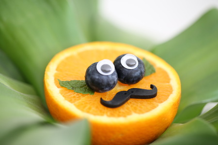 Photo pour Slice of the orange is funny decorated as if a clowns face, make it appealing for kids to eat the fruits. - image libre de droit