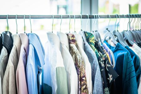 Photo pour Summer wardrobe showcase. White and gray tone knitwear hanging on a coat rack. Selective focus, horizontal. - image libre de droit