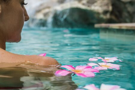 Foto de female in a swimming pool. Tropical flowers Frangipani Plumeria, Leelawadee floating in the water. Spa pool. Peace and tranquility. Spa concept - Imagen libre de derechos